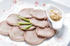 Βρασμένη γλώσσα βόειου κρέατος με το χρένο και χορτάρια στο άσπρο εξυπηρετώντας πιάτο και τον ξύλινο πίνακα Εκλεκτική εστίαση Στοκ εικόνες με δικαίωμα ελεύθερης χρήσης