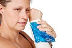 Βραχίονας γυναίκας με το παυσίπονο επιδέσμων και πάγου στοκ εικόνες