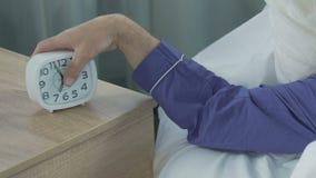 Βραχίονας του αρσενικού που φθάνει στο ρολόι για να ελέγξει το χρόνο, ξυπνητήρι στα ξημερώματα, εργάσιμη μέρα απόθεμα βίντεο