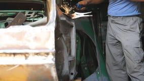 Το αρσενικό χέρι του επισκευαστή ή του μηχανικού εργαζομένου ενώνει στενά τα μέρη μετάλλων του παλαιού αυτοκινήτου με τη μηχανή σ απόθεμα βίντεο