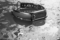 Βραχιόλι ικανότητας σε ένα μαύρο υπόβαθρο πλακών με τις πτώσεις του νερού Στοκ Εικόνες