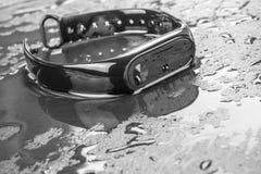 Βραχιόλι ικανότητας σε ένα μαύρο υπόβαθρο πλακών με τις πτώσεις του νερού Στοκ Φωτογραφίες