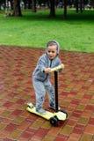 Βρεγμένο στη βροχή, ένα αγόρι σε ένα αθλητικό κοστούμι κάνει πατινάζ σε ένα μηχανικό δίκυκλο Περίπατος άνοιξη στο πάρκο πόλεων, β Στοκ Φωτογραφίες