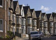 Βρετανικά σπίτια σε μια σειρά με το αυτοκίνητο που σταθμεύουν στην οδό Στοκ Εικόνα