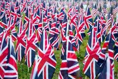 Βρετανικές Ηνωμένες UK σημαίες σε μια σειρά με την μπροστινή εστίαση και τα πιό πέρα σύμβολα μουτζουρωμένος με το bokeh Οι σημαίε Στοκ Εικόνες