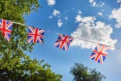Βρετανικές σημαίες υφάσματος του Union Jack ενάντια στον ουρανό και τα πράσινα δέντρα Στοκ Εικόνες