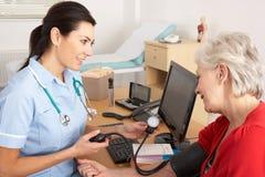 Βρετανική νοσοκόμα που παίρνει τη πίεση του αίματος της γυναίκας Στοκ φωτογραφία με δικαίωμα ελεύθερης χρήσης
