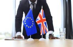 Βρετανική σημαία και σημαία της Ευρωπαϊκής Ένωσης με τον επιχειρηματία πλησίον κοντά Brexit Στοκ Εικόνες
