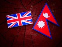 Βρετανική σημαία με τη σημαία Nepali σε ένα κολόβωμα δέντρων που απομονώνεται Στοκ φωτογραφία με δικαίωμα ελεύθερης χρήσης