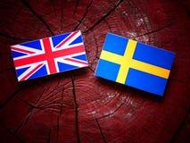 Βρετανική σημαία με τη σουηδική σημαία σε ένα κολόβωμα δέντρων Στοκ φωτογραφία με δικαίωμα ελεύθερης χρήσης