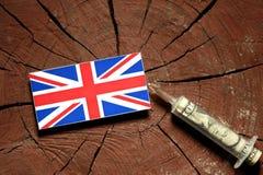 Βρετανική σημαία σε ένα κολόβωμα με τη σύριγγα που εγχέει τα χρήματα Στοκ Φωτογραφία