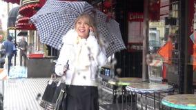 βροχή Γυναίκα που περπατά κάτω από ένα πεζοδρόμιο πόλεων που κρατά την ομπρέλα της απόθεμα βίντεο