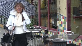 βροχή Γυναίκα που περπατά κάτω από ένα πεζοδρόμιο πόλεων που κρατά την ομπρέλα της φιλμ μικρού μήκους