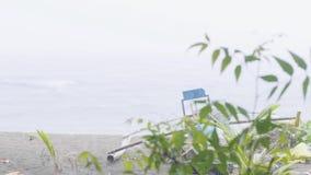 Βροχή στην παραλία θάλασσας, το αλιευτικό σκάφος και το πράσινο υπόβαθρο κλάδων Θυελλώδης θάλασσα ενώ καιρός βροχής στην αμμώδη π απόθεμα βίντεο