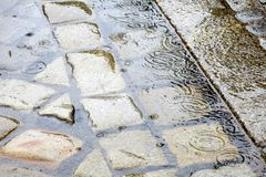 Βροχή στην πόλη - λακκούβες στο πεζοδρόμιο οδών κυβόλινθων - Στοκ φωτογραφία με δικαίωμα ελεύθερης χρήσης