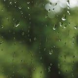 Βροχερή θερινή ημέρα, σταγόνες βροχής στο υγρό γυαλί παραθύρων, φωτεινή αφηρημένη λεπτομέρεια σχεδίων υποβάθρου νερού βροχής, μακ Στοκ Φωτογραφίες