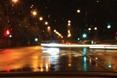 Βροχερή οδός νύχτας μέσω του ανεμοφράκτη Στοκ φωτογραφία με δικαίωμα ελεύθερης χρήσης