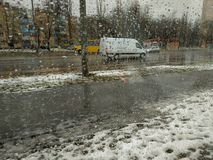 Βροχερή χειμερινή ημέρα στην πόλη, άποψη μέσω ενός υγρού παραθύρου στην οδό στοκ εικόνες