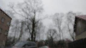 Βροχερός θλιβερός καιρός που αντιμετωπίζεται από μέσα ενός αυτοκινήτου με τις ψήκτρες που αφαιρούν ενεργά τις πτώσεις βροχής από  απόθεμα βίντεο