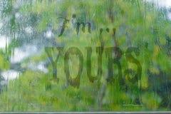 Βροχερό κείμενο που γράφεται στο ομιχλώδες παράθυρο στοκ εικόνα με δικαίωμα ελεύθερης χρήσης