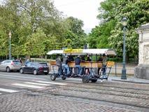 ΒΡΥΞΕΛΛΕΣ - 26 ΑΠΡΙΛΊΟΥ: Τουρίστες που οδηγούν το ποδήλατο μπύρας κοντά στο βασιλικό πάρκο στις Βρυξέλλες Φωτογραφία που λαμβάνετ στοκ φωτογραφίες