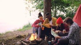 Βρόχος Cinemagraph - ευτυχείς φίλοι νέων που εξετάζουν τους χάρτες που κάθονται στο δάσος γύρω από την πυρκαγιά και που κρατούν τ φιλμ μικρού μήκους