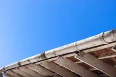 Βρώμικα ζευκτόντα υδρορροών και στεγών ενάντια στο μπλε ουρανό Στοκ φωτογραφία με δικαίωμα ελεύθερης χρήσης