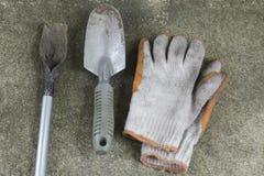 Βρώμικα και παλαιά φτυάρια και γάντια κήπων στο τσιμεντένιο πάτωμα στοκ εικόνα