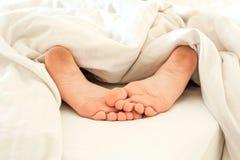 Βρώμικα πόδια παιδιών ύπνου στα άσπρα κλινοσκεπάσματα από την πίσω πλευρά Στοκ εικόνα με δικαίωμα ελεύθερης χρήσης
