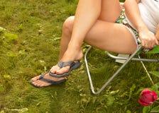 Βρώμικα σαγιονάρες και πόδια στη χλόη, τη συνεδρίαση γυναικών και τη στήριξη στην καρέκλα στον κήπο της μετά από τη σκληρή δουλει Στοκ Εικόνες