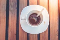 Βρώμικα φλυτζάνι και κουτάλι καφέ που θέτουν στο άσπρο πιατάκι και τον ξύλινο πίνακα μετά από να πιει το πρωί στρέψτε μαλακό Στοκ Εικόνες