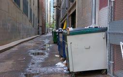 Βρώμικη ακάθαρτη πίσω αλέα με τα dumpsters και τα απορρίμματα Στοκ Φωτογραφία