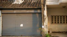 Βρώμικη εκλεκτής ποιότητας πόρτα παραθυρόφυλλων κυλίνδρων με την κενή σημείωση εγγράφου - παλαιό αβ στοκ εικόνα