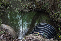 Βρώμικοι μίσχοι νερού από το σωλήνα που μολύνει τον ποταμό Στοκ φωτογραφία με δικαίωμα ελεύθερης χρήσης