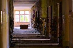 Βρώμικος διάδρομος σε ένα εγκαταλειμμένο κτήριο με το φως που προέρχεται από τα δωμάτια στο δικαίωμα στοκ φωτογραφίες με δικαίωμα ελεύθερης χρήσης