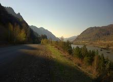 Βρώμικος δρόμος που βρίσκεται κατά μήκος της όχθης ποταμού και του ποδιού των υψηλών βουνών στοκ φωτογραφίες