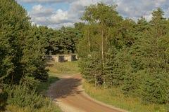 Βρώμικος δρόμος που οδηγεί στις αποθήκες στο δάσος στην παλαιά στρατιωτική βάση Karosta, Liepaja Στοκ Φωτογραφία