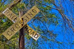 Βρώμικος δρόμος ραγών που διασχίζει το σημάδι στην ξύλινη θέση Στοκ φωτογραφίες με δικαίωμα ελεύθερης χρήσης