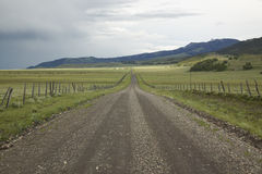 Βρώμικος δρόμος στην εκατονταετή κοιλάδα, Μοντάνα με την εισερχόμενη θύελλα, τους πράσινους τομείς και τα βουνά Στοκ Εικόνες