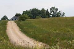 Βρώμικος δρόμος χώρας με το παλαιό σπίτι ανεμελιάς Στοκ Εικόνες