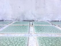 Βρώμικος συμπαγής τοίχος και πράσινο δωμάτιο κεραμωμένων πατωμάτων ως υπόβαθρο, για το διάστημα αντιγράφων Στοκ Φωτογραφίες