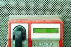 Βρώμικο ανθυγιεινό κόκκινο δημόσιο τηλέφωνο που καλύπτεται με την κινηματογράφηση σε πρώτο πλάνο ανώτερων μερών σκόνης Στοκ Φωτογραφίες