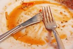 Βρώμικο πιάτο μετά από να φάει Το βρώμικο δίκρανο και το βρώμικο μαχαίρι βρίσκονται Στοκ Φωτογραφία