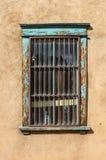 Βρώμικο φραγμένο παράθυρο στον τοίχο στόκων με το ξεφλούδισμα του τυρκουάζ χρώματος στοκ εικόνες