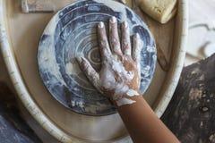 Βρώμικο χέρι του αγγειοπλάστη στον άσπρο άργιλο στη ρόδα αγγειοπλαστών ` s Στοκ εικόνες με δικαίωμα ελεύθερης χρήσης