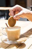 Βυθίζοντας μια ολλανδική βάφλα καραμέλας, αποκαλούμενη Stroopwafel, στον καφέ στοκ εικόνες