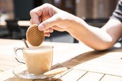 Βυθίζοντας μια ολλανδική βάφλα καραμέλας, αποκαλούμενη Stroopwafel, στον καφέ στοκ φωτογραφία