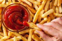 Βυθίζοντας τηγανιτές πατάτες χεριών στη σάλτσα ή το κέτσαπ ντοματών Στοκ Εικόνες