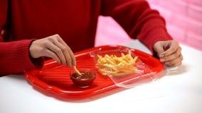 Βυθίζοντας τηγανιτή πατάτα γυναικών στο κέτσαπ, ανθυγειινή διατροφή, εστιατόριο γρήγορου φαγητού στοκ εικόνες