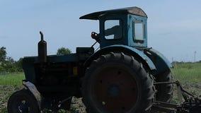 Βωλοκόποι τρακτέρ ένας αγρο τομέας το καλοκαίρι σε σε αργή κίνηση απόθεμα βίντεο
